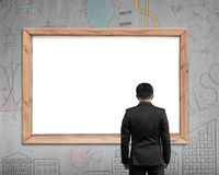 Businessman looking at wooden frame with blank white view Stock Photography