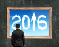 Businessman looking at wooden frame white 2016 arrow up clouds. Rear view businessman looking at wooden frame with view of white 2016 arrow up clouds, on old Stock Image