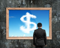 Businessman looking at wooden frame white dollar sign shape clou Stock Photos
