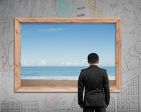 Businessman looking at wooden frame window with sea beach Royalty Free Stock Image