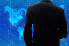Businessman looking at world map. Back side of businessman in dark gray suit when he is looking at world map and thinking about global business Royalty Free Stock Photo