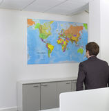Businessman Looking At World Map In Office Royalty Free Stock Photos