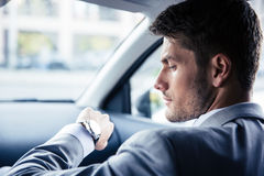 Businessman looking on wrist watch Stock Photos