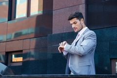 Businessman looking on wrist watch outdoors. Near office building Stock Photos