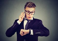 Businessman looking at wrist watch, talking on mobile phone running late for meeting. Time is money Stock Images