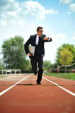 Businessman looking wrist watch watch running on athletic track in stress Stock Images