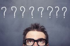 Question Marks. Businessman lookip up question marks on blackboard Stock Photography