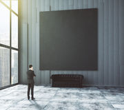 Businessman looks at big blank picture stock photo