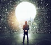 Businessman looks at a big hole on the wall shaped as a light bulb royalty free stock photo