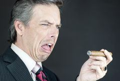 Businessman Looks At Cigar In Disgust Stock Photography