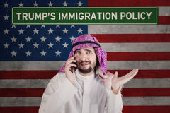 Businessman looks confused with American policy. Arabian businessman looks confused while talking on mobile phone standing in front of an American flag with Stock Photography