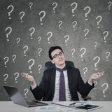 Businessman looks confused with question sign Royalty Free Stock Photography