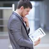 Businessman looks at digital tablet screen with the digital schedule.  royalty free stock images
