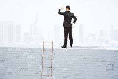 Businessman looks into the distance on the top of white brick wa Royalty Free Stock Images