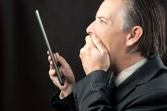 Businessman Looks At His Tablet Amazed Royalty Free Stock Images