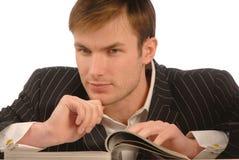 Businessman looks magazine Stock Photos