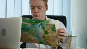 A businessman with looks at a map in the office.  stock video
