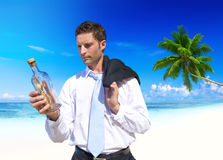 Businessman Looks at Message in a Bottle Royalty Free Stock Images