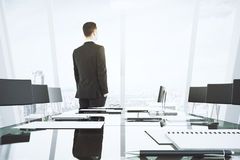 Businessman looks out the window in conference room with glassy Royalty Free Stock Photography