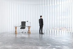 Businessman looks out the window in empty loft room with glassy Royalty Free Stock Images