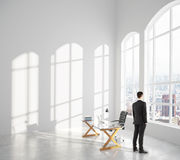 Businessman looks out the window in loft interior room with glas Royalty Free Stock Photography