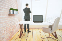 Businessman looks out the window in loft room with laptop with b Stock Photography