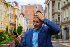The businessman looks in phone. tests a shock and surprise. royalty free stock image