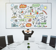 Businessman looks at the poster with business scheme and conference table with chairs stock photography