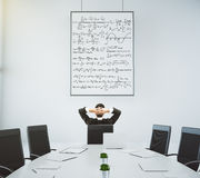 Businessman looks at the poster with equations in modern confere Stock Photography