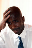 Businessman looks sad. An african black businessman looks sad stock image