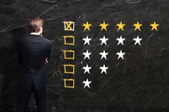 Businessman looks at a 5 star rating. On a chalkboard stock photography