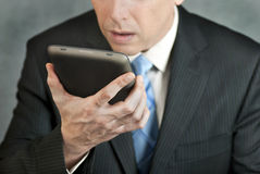 Businessman Looks At Tablet With Despair Stock Photo