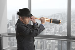 Businessman looks through a telescope Stock Photography