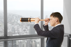 Businessman looks through a telescope Stock Photo