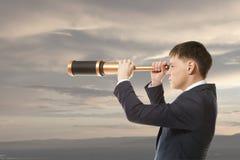Businessman looks through a telescope Stock Photography