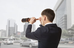 Businessman looks through a telescope Royalty Free Stock Photo