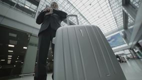 Businessman looks on ticket and talks on phone in the airport. Handsome businessman wearing the suit stands in the airport hall. Attractive man dials on his stock footage