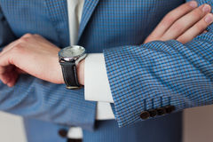 Businessman looks the time on his wristwatch. Closeup royalty free stock images