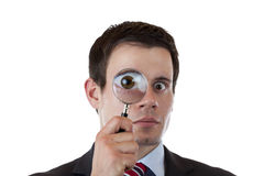 Businessman looks trhough magnifying lens Royalty Free Stock Photo
