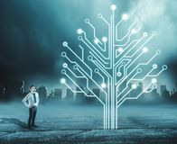 Circuit board tree. Businessman looks up to the circuit board tree in urban background stock images