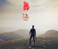 Businessman Loser. Businessman is losing a big piggy, flying away with some balloons Stock Photo