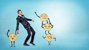 A businessman losing his balance while many large golden coins with arms and legs are trying to make him fall. Hard earned money. Financial pitfalls. Small and Stock Photo