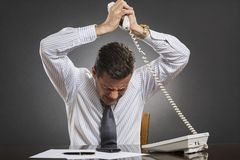 Businessman losing temper control. Nervous frustrated businessman wearing white shirt and tie losing temper control after receiving bad news on the phone over Stock Photo
