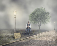 Businessman that Lost a Job. Businessman Sitting on Bench in Misty Park with Title I Need Job-Job Loss Concept Royalty Free Stock Photo