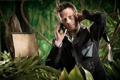 Businessman lost in jungle calling for help Stock Photo