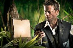 Businessman lost in jungle Stock Photo