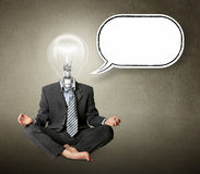 Businessman in lotus pose and lamp-head. With thought bubble Royalty Free Stock Images