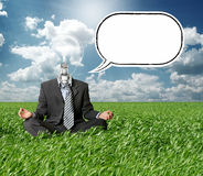 Businessman in lotus pose and lamp-head in grass. Businessman in lotus pose and lamp-head with thought bubble in green grass on blue summer sky Royalty Free Stock Photos