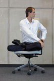 Businessman in lotus pose on office chair practicing yoga Royalty Free Stock Image