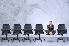 Businessman in lotus posture. Flying in air on grey background Stock Images